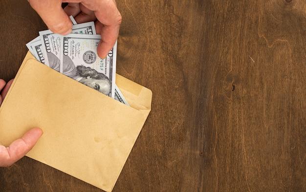 Mannenhand haalt geld uit papieren envelop