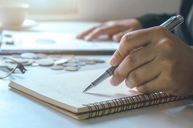 Mannenhand, handtekening, documenten invullen of aantekeningen maken over financiële documenten.