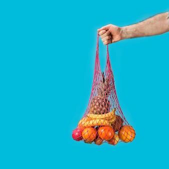 Mannenhand houdt een boodschappentas met boodschappentassen - ananas, sinaasappelen. zorgzame concept ecologie