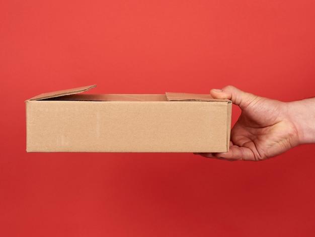 Mannenhand houdt een bruine kartonnen doos op een rode achtergrond