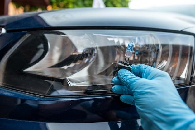 Mannenhand houdt een halogeenlamp tegen de koplampen, allemaal voor reparatieauto's
