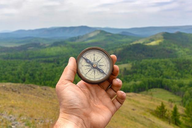 Mannenhand houdt een magnetisch kompas vast op de achtergrond van heuvels en de lucht