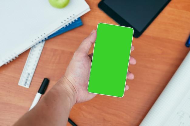 Mannenhand houdt een smartphone met leeg scherm boven bureau met briefpapier, universiteit, hogeschool