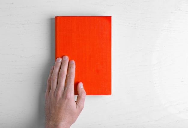 Mannenhand houdt het rode boek op witte tafel.