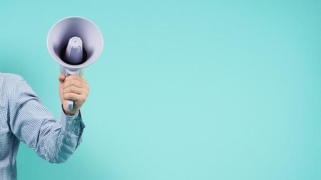 Mannenhand houdt megafoon vast en draagt een blauw shirt op een groene of mintgroene of tiffany blue-achtergrond.