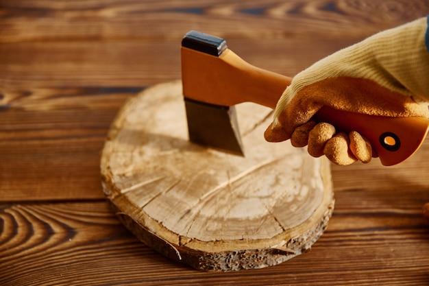 Mannenhand in handschoen houdt een bijl, close-up, houten tafel. professioneel instrument, timmermansuitrusting, houtbewerkingsgereedschap