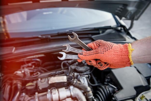 Mannenhand in handschoen met sleutels tegen automotor