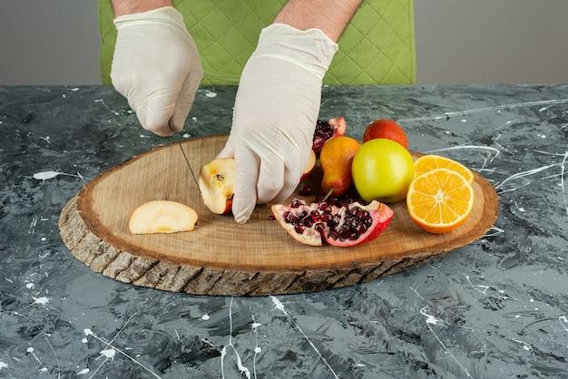 Mannenhand in handschoenen die verse appel op marmeren lijst snijden.