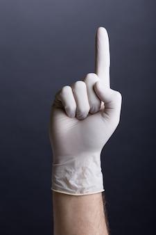 Mannenhand in latex handschoen (vinger omhoog)