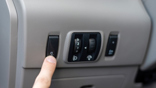 Mannenhand indrukken van een knop in een elektrische auto