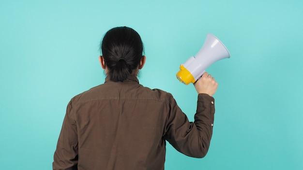 Mannenhand is een megafoon in de hand en draagt een marineblauw overhemd op een groene of mintgroene of tiffany blue-achtergrond.