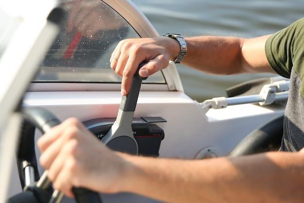 Mannenhand is op de bedieningshendel van een witte motorboot close-up