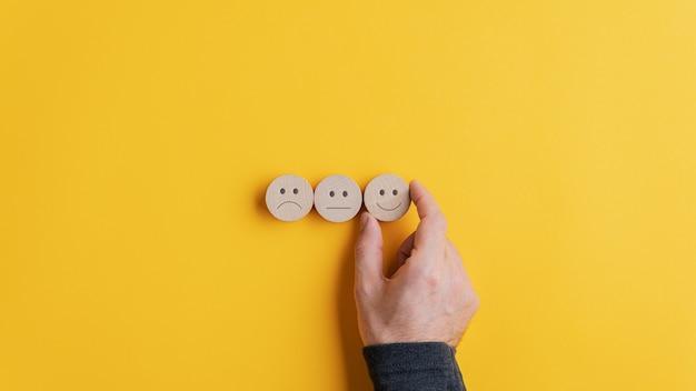 Mannenhand kiezen van een lachend gezicht optie uit de rij van drie keuzes