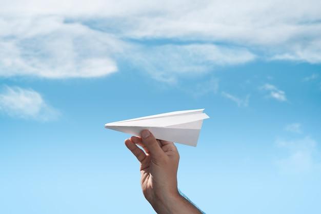 Mannenhand lanceert papieren origamivliegtuig.