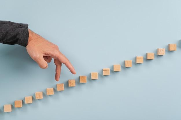 Mannenhand lopen zijn vingers de trap gemaakt van houten blokken.