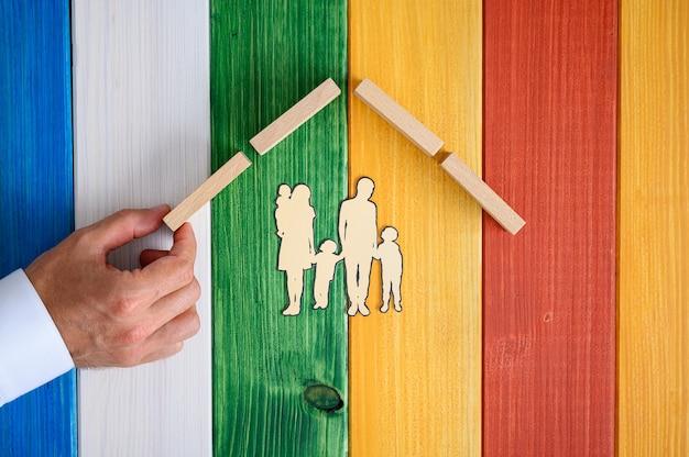 Mannenhand maken van een dak boven een papier gesneden silhouet van een gezin in een conceptueel beeld. over kleurrijke houten achtergrond.