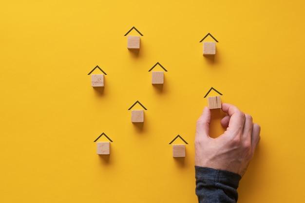 Mannenhand maken veel huizen van houten blokken in een conceptueel beeld van onroerend goed en stadsplanning.