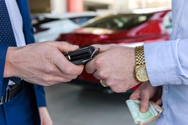 Mannenhand met autosleutels tegen nieuwe auto in showroom
