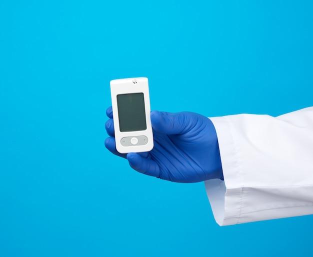 Mannenhand met blauwe steriele handschoenen heeft een witte bloedglucosemeter voor het meten van de bloedsuikerspiegel