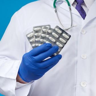 Mannenhand met blauwe steriele handschoenen houdt een stapel pillen in een blister