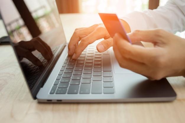 Mannenhand met creditcard en met behulp van laptop online winkelconcept