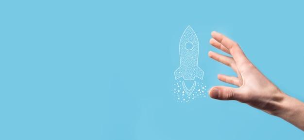 Mannenhand met digitale transparante raket pictogram. opstarten bedrijfsconcept. raket lanceert en zweeft vliegen. concept van bedrijfsidee.