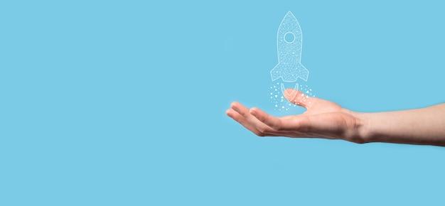 Mannenhand met digitale transparante raket pictogram. opstarten bedrijfsconcept.