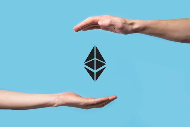 Mannenhand met een ethereum-pictogram op blauwe achtergrond. ethereum en cryptocurrency-investeringsconcept. het uitwisselen, verhandelen, overdragen en investeren van blockchain-technologie.