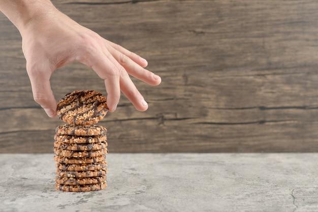 Mannenhand met een havermoutkoekje met chocoladesiroop op een houten.