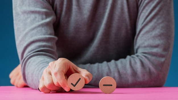 Mannenhand met een houten gesneden cirkel met een vinkje erop met een andere cirkel met minteken