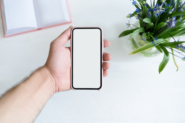 Mannenhand met een smartphone. wit leeg scherm. tafel met laptop en bloemen op