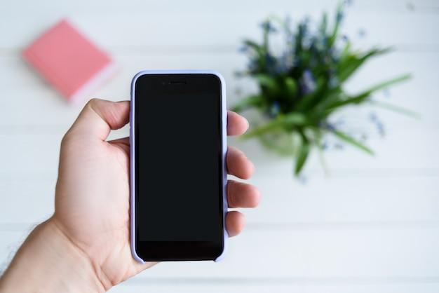 Mannenhand met een smartphone. zwart leeg scherm. tafel met laptop en bloemen