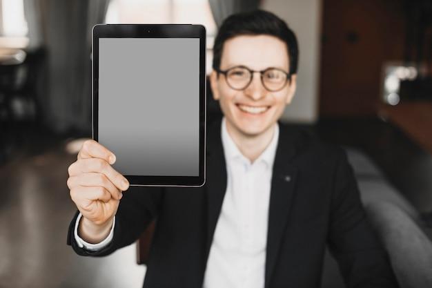 Mannenhand met een tabletscherm tijdens het kijken naar camera glimlachend gekleed in pak en bril.