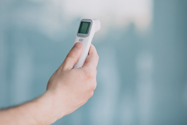 Mannenhand met electro thermometer