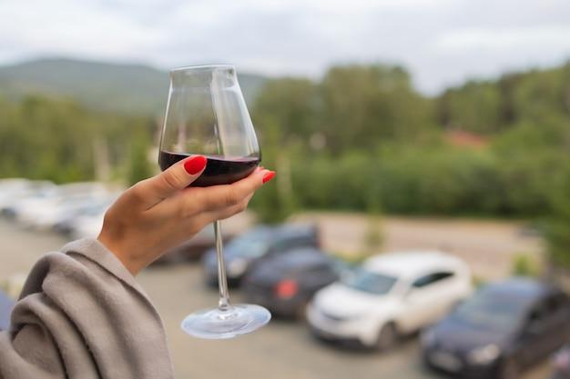 Mannenhand met glas met wijn op onscherpe natuurlijke achtergrond.