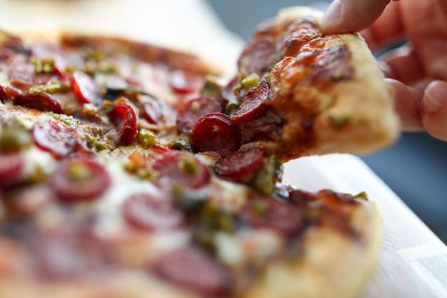 Mannenhand met groot stuk lekkere verse pizza close-up