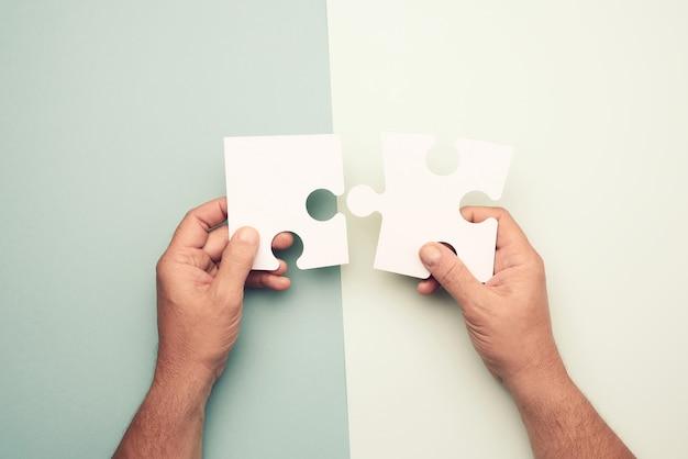 Mannenhand met grote papieren witte lege puzzelstukjes