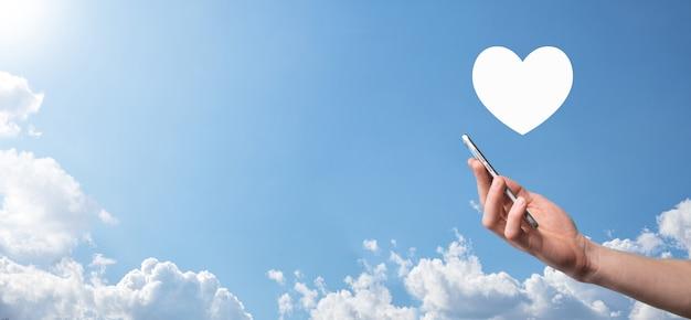 Mannenhand met hart, zoals pictogram op blauwe achtergrond. vriendelijkheid, liefdadigheid, pure liefde en mededogen concept. banner met kopie ruimte.