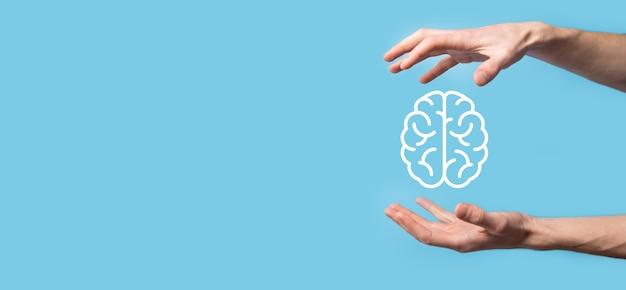 Mannenhand met hersenen pictogram op blauwe achtergrond. kunstmatige intelligentie machine learning internet technologie bedrijfsconcept. banner met kopie ruimte.