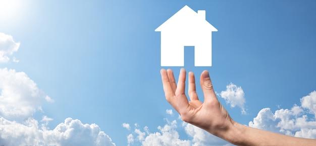 Mannenhand met huisje op blauwe achtergrond. vastgoedverzekering en veiligheidsconcept. onroerend goed
