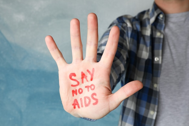 Mannenhand met inscriptie zeg nee tegen aids op blauwe muur, ruimte voor tekst