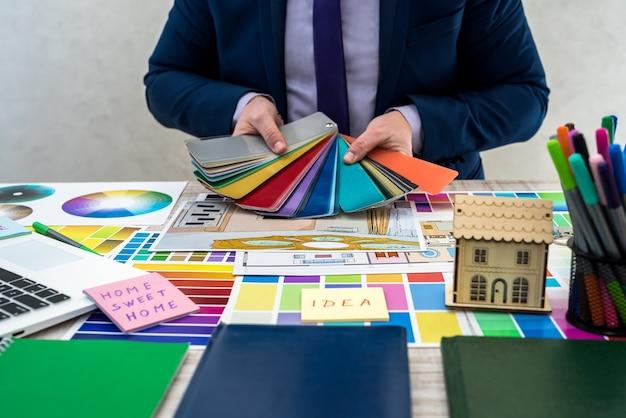 Mannenhand met kleurstalen met interieur perspectief. de hand van een interieurontwerper die met appartementschets, materiaal- en kleurstalen werkt