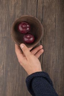 Mannenhand met kom met sappige pruimen op houten oppervlak