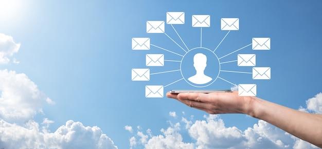 Mannenhand met letterpictogram, e-mailpictogrammen. neem contact met ons op via nieuwsbrief-e-mail en bescherm uw persoonlijke gegevens tegen spammail. klantenservice callcenter neem contact met ons op.e-mailmarketing en nieuwsbrief Premium Foto