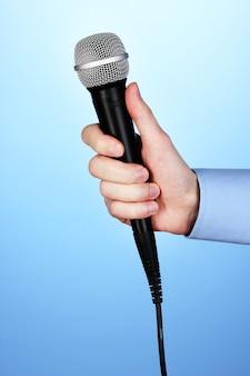 Mannenhand met microfoon op blauw