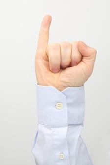 Mannenhand met opgeheven pink op een witte achtergrond