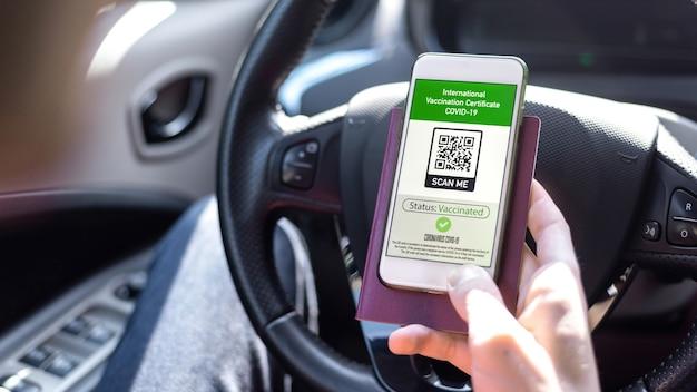 Mannenhand met paspoort en smartphone met internationaal vaccinatiecertificaat covid-19 qr-code in een auto