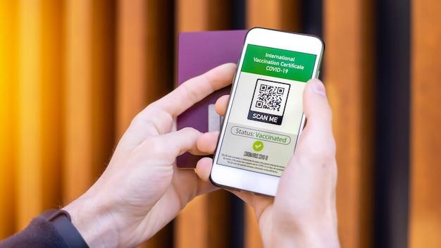 Mannenhand met paspoort en smartphone met internationaal vaccinatiecertificaat covid-19 qr-code