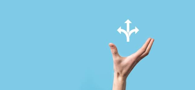 Mannenhand met pictogram met drie richtingen pictogram op blauwe achtergrond twijfel niet te moeten kiezen tussen drie verschillende keuzes aangegeven door pijlen die wijzen in tegengestelde richting concept drie manieren
