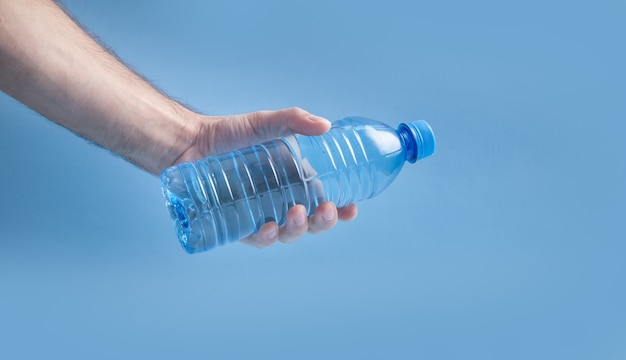 Mannenhand met plastic waterfles.